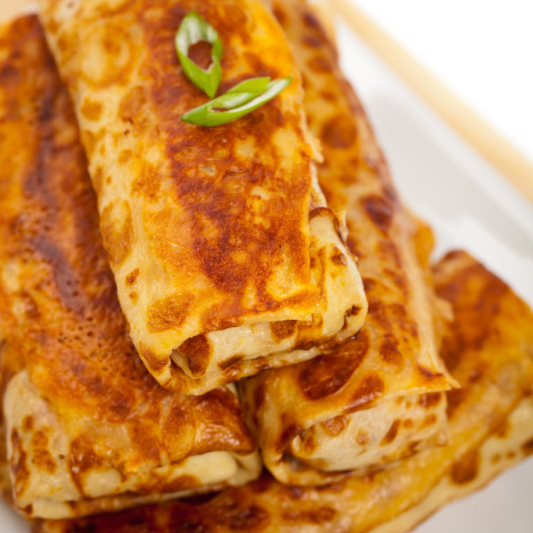 Russian Stuffed Pancakes Blintzes with Meat Isolated on White. Selective focus.